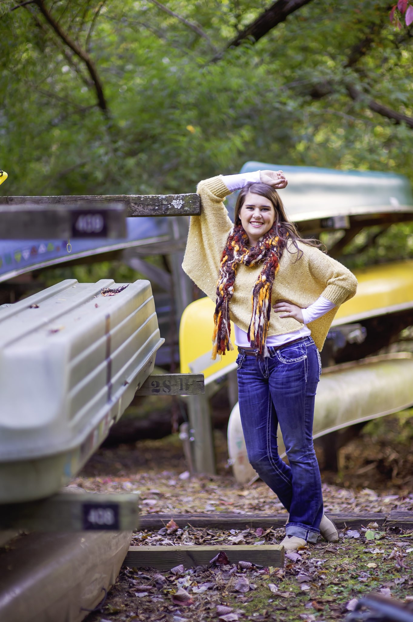 young white woman posing for a picture by canoes