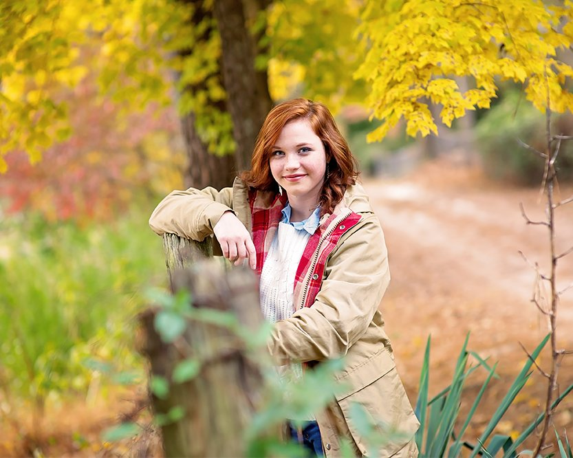 young woman posing for a picture in autumn by a fence