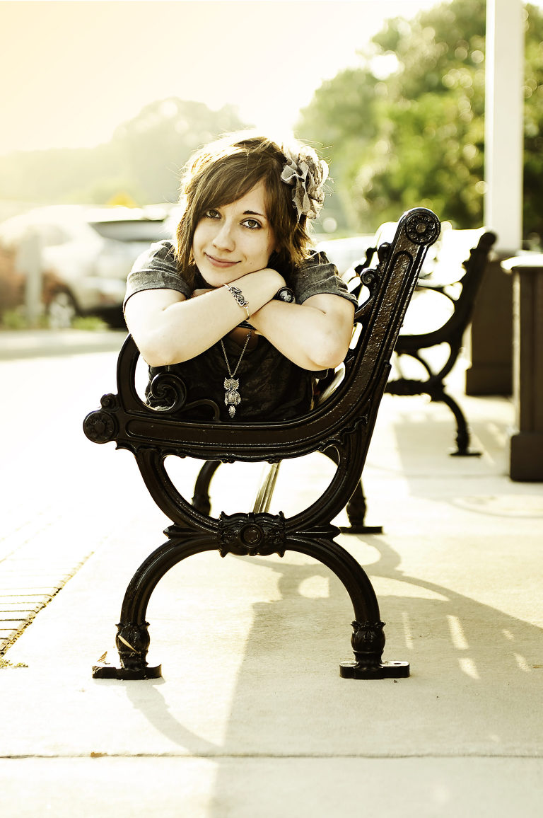 young woman on a bench arms crossed