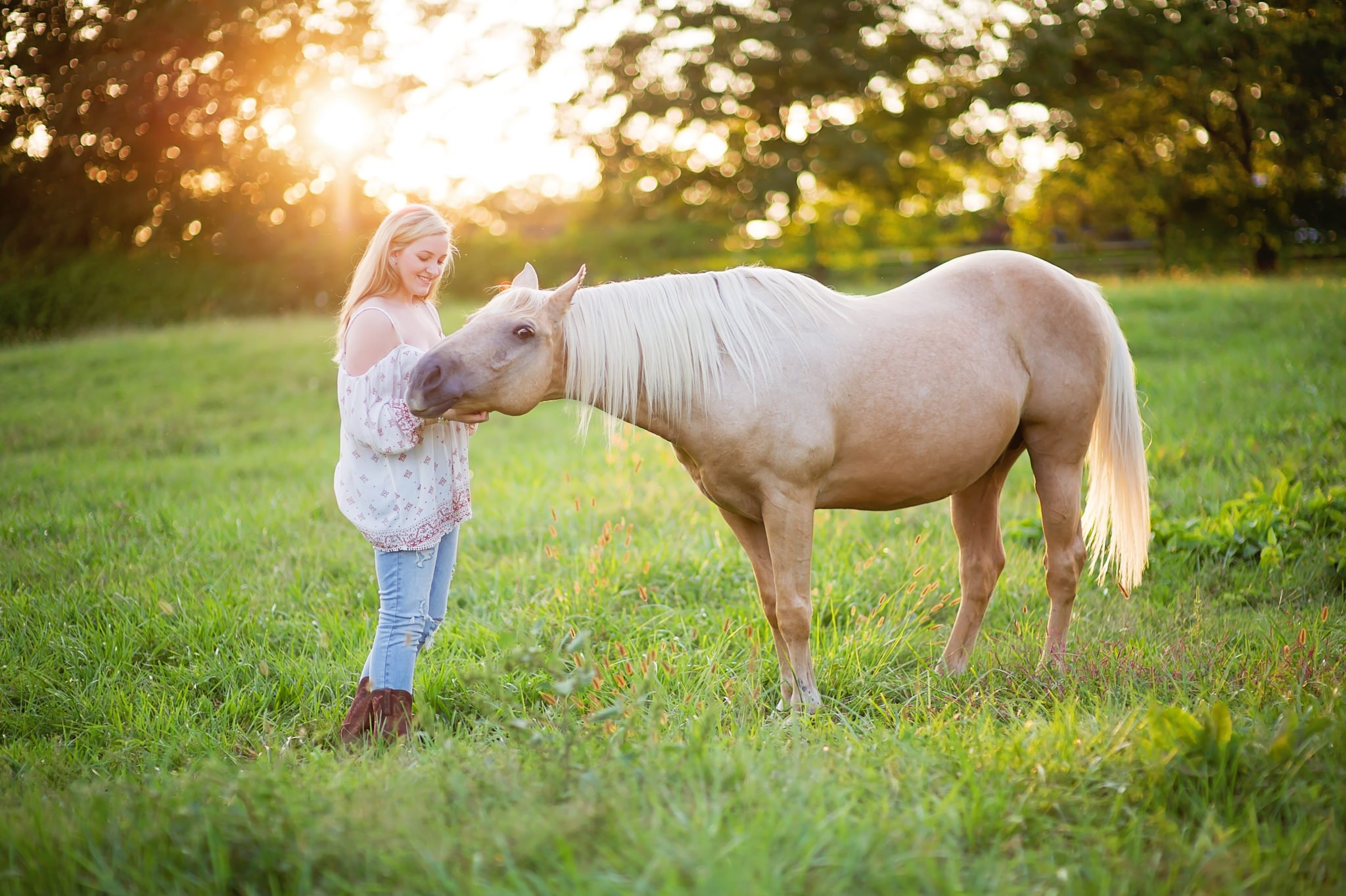young woman with a horse in a field at sunset