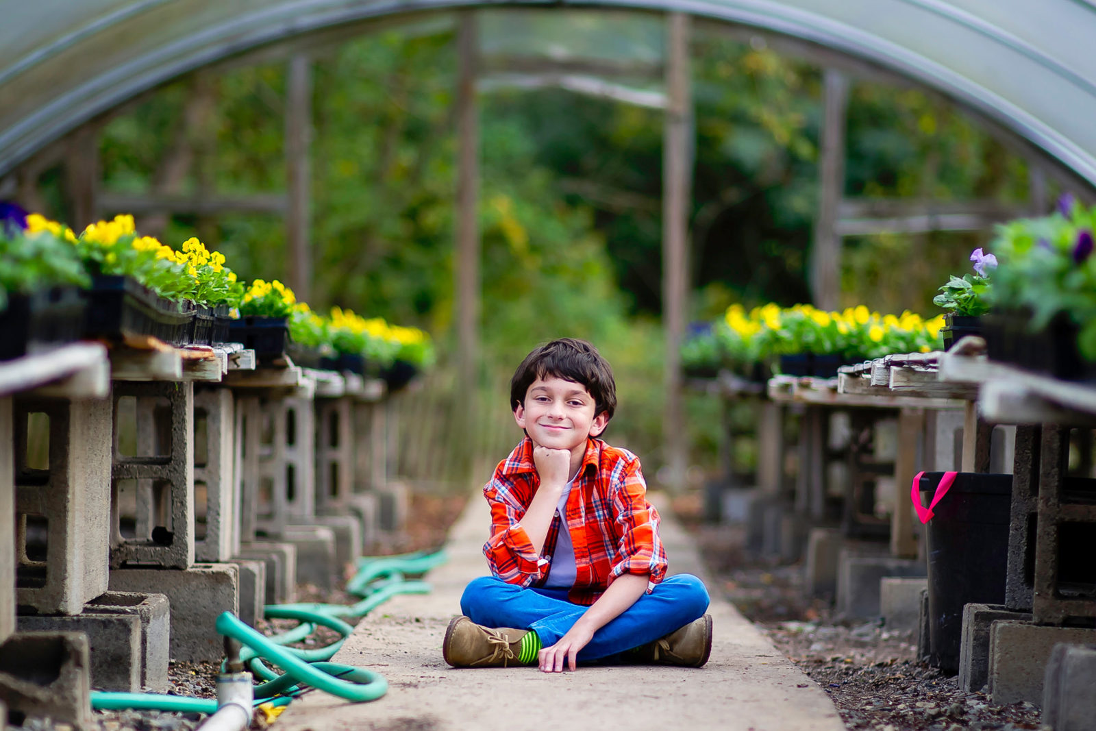 Boy wearing orange plaid shirt and blue pants sitting cross legged in a nursery with pansy flowers