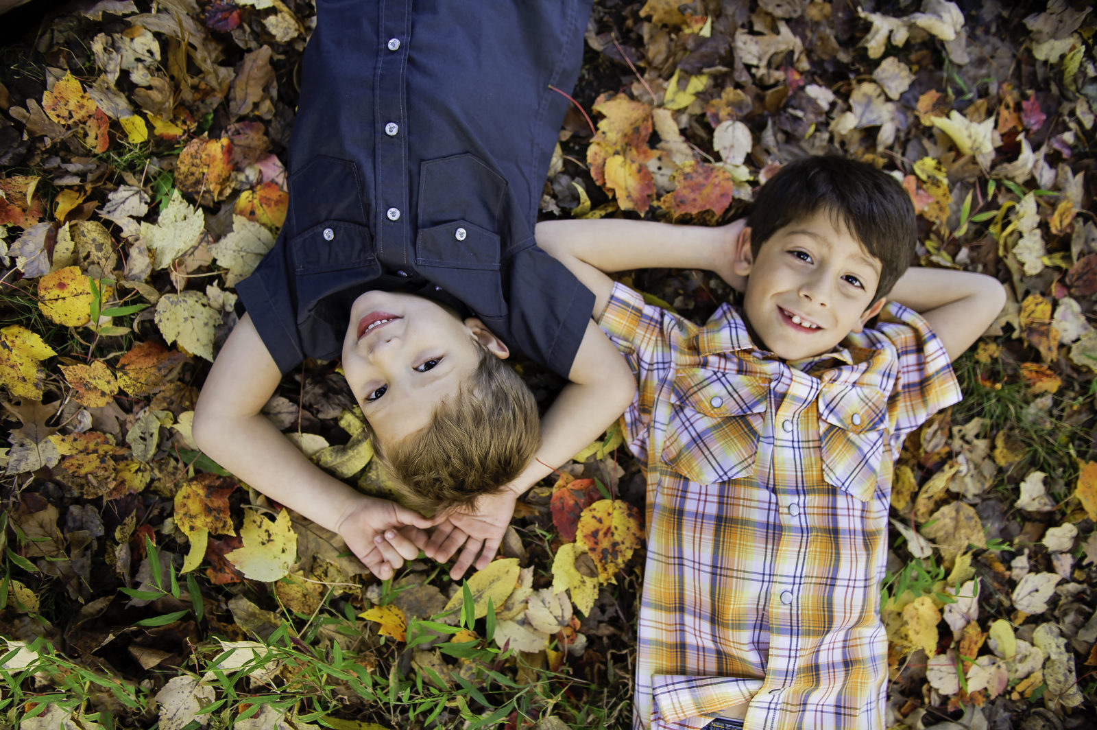 young boys laying fall leaves smiling