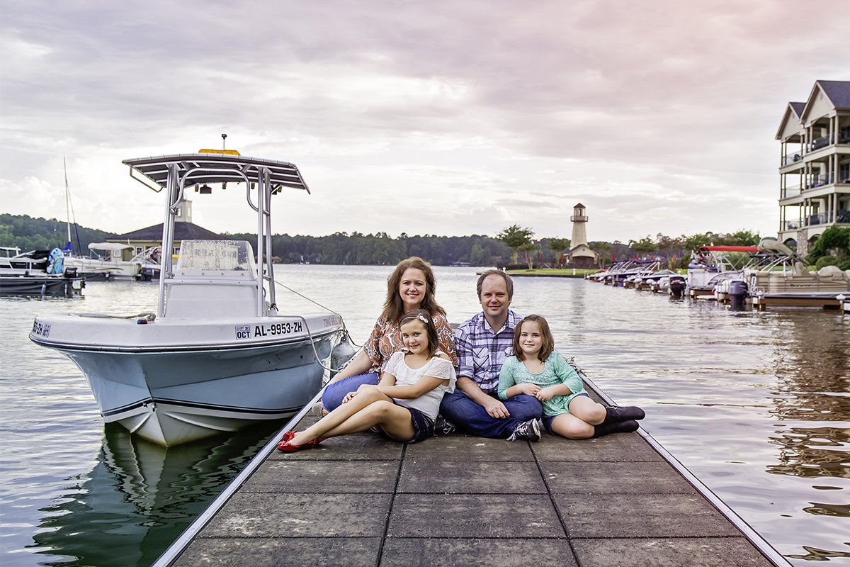 family posing for a picture on a boat dock by a marina