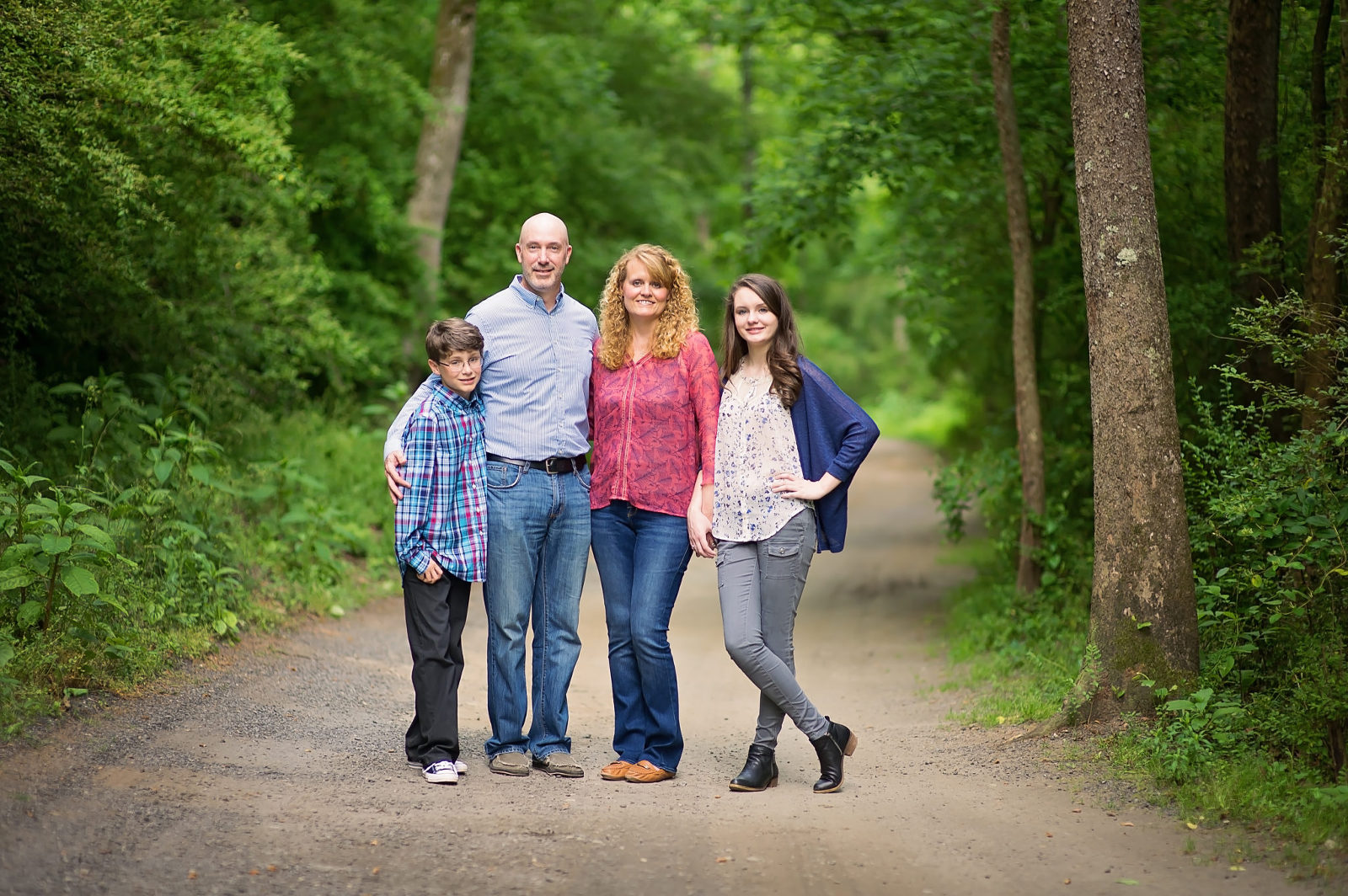 family posing standing for a picture on a wooded trail