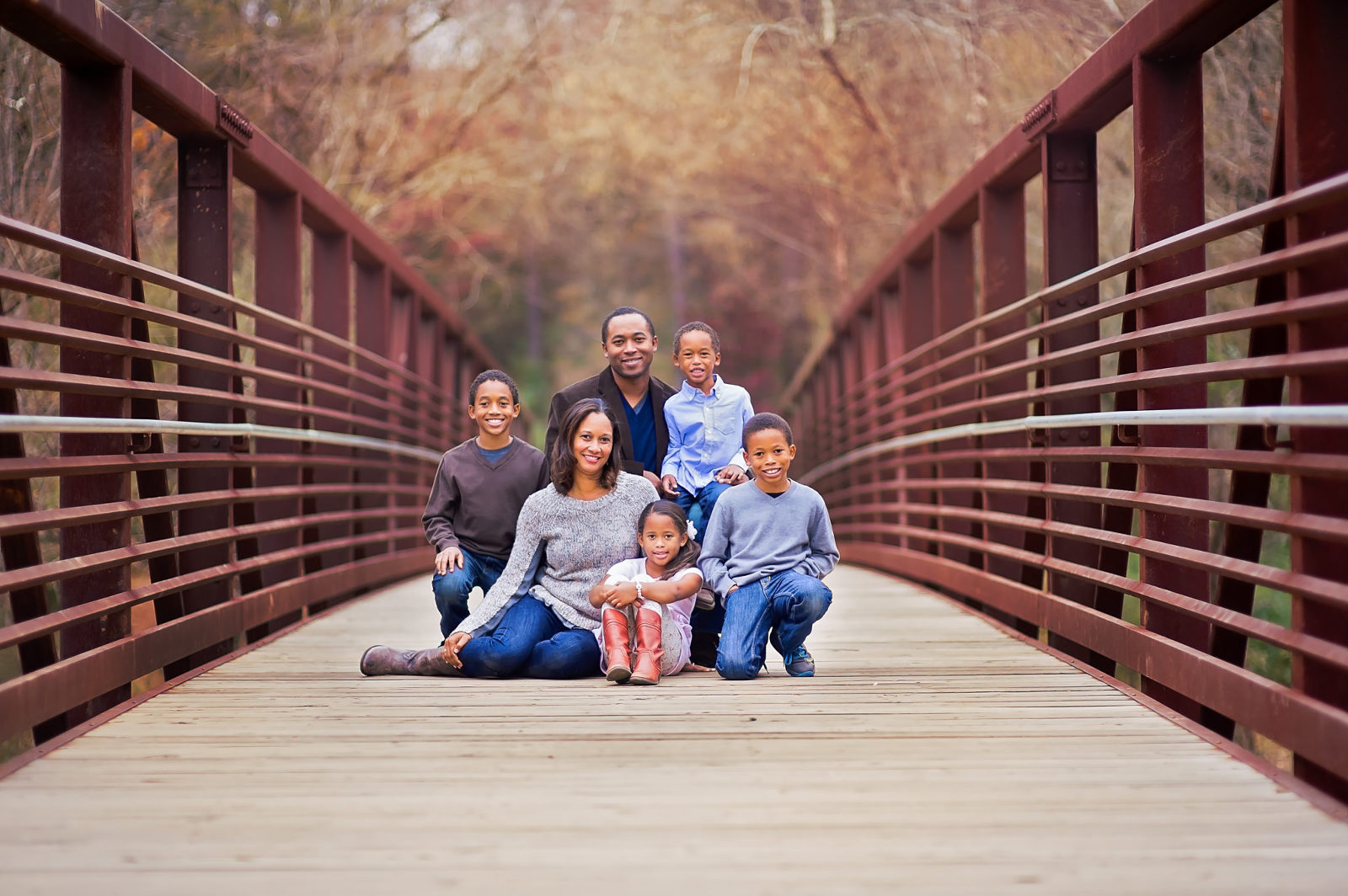 family posing on a bridge for a family picture