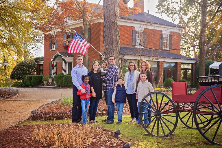 family and children posing for a picture with an American flag in front of a brick building