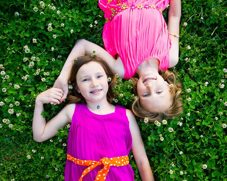 young girls sisters laying in clover smiling holding hands
