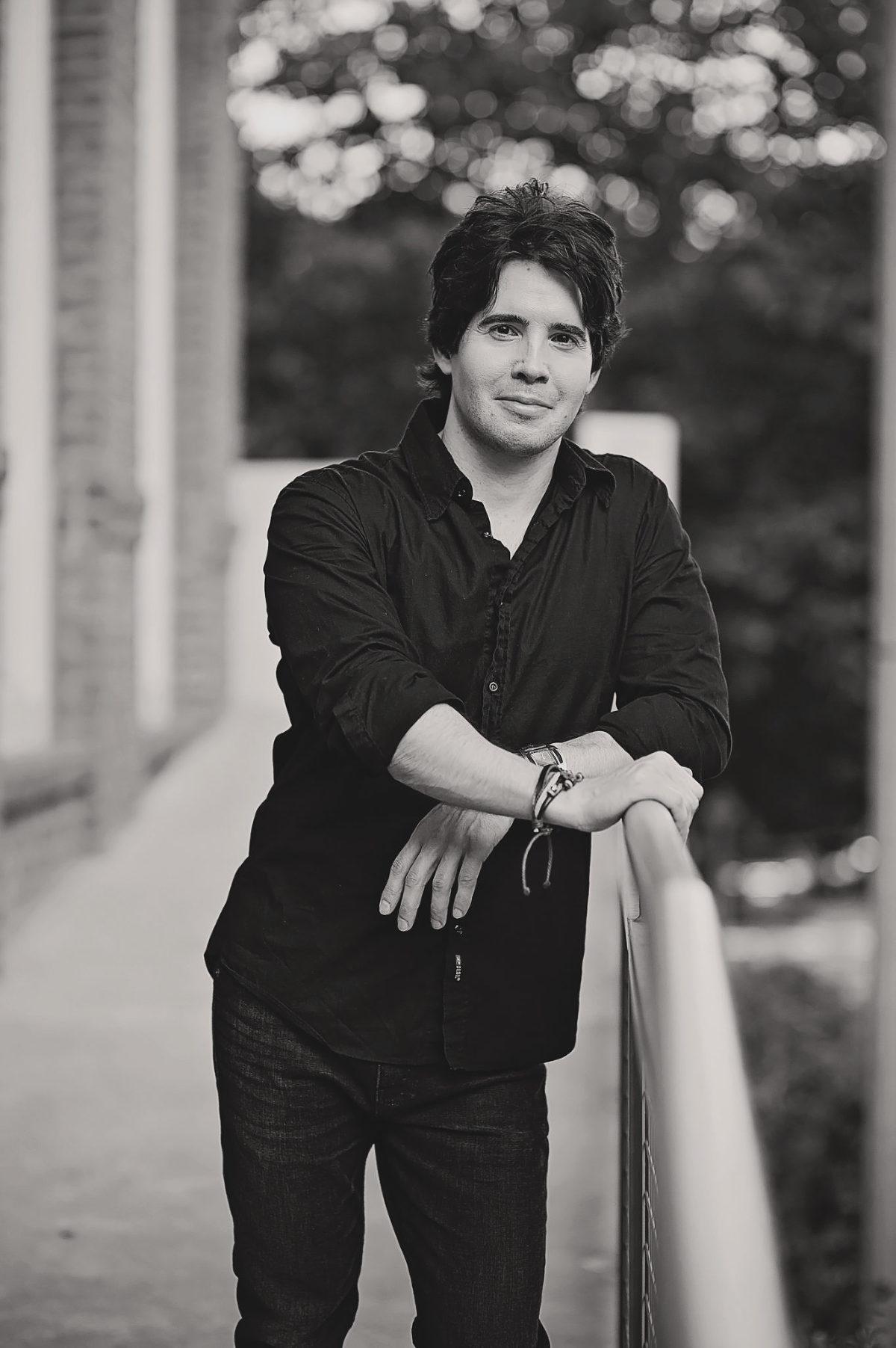 man wearing a black shirt standing by a porch rail