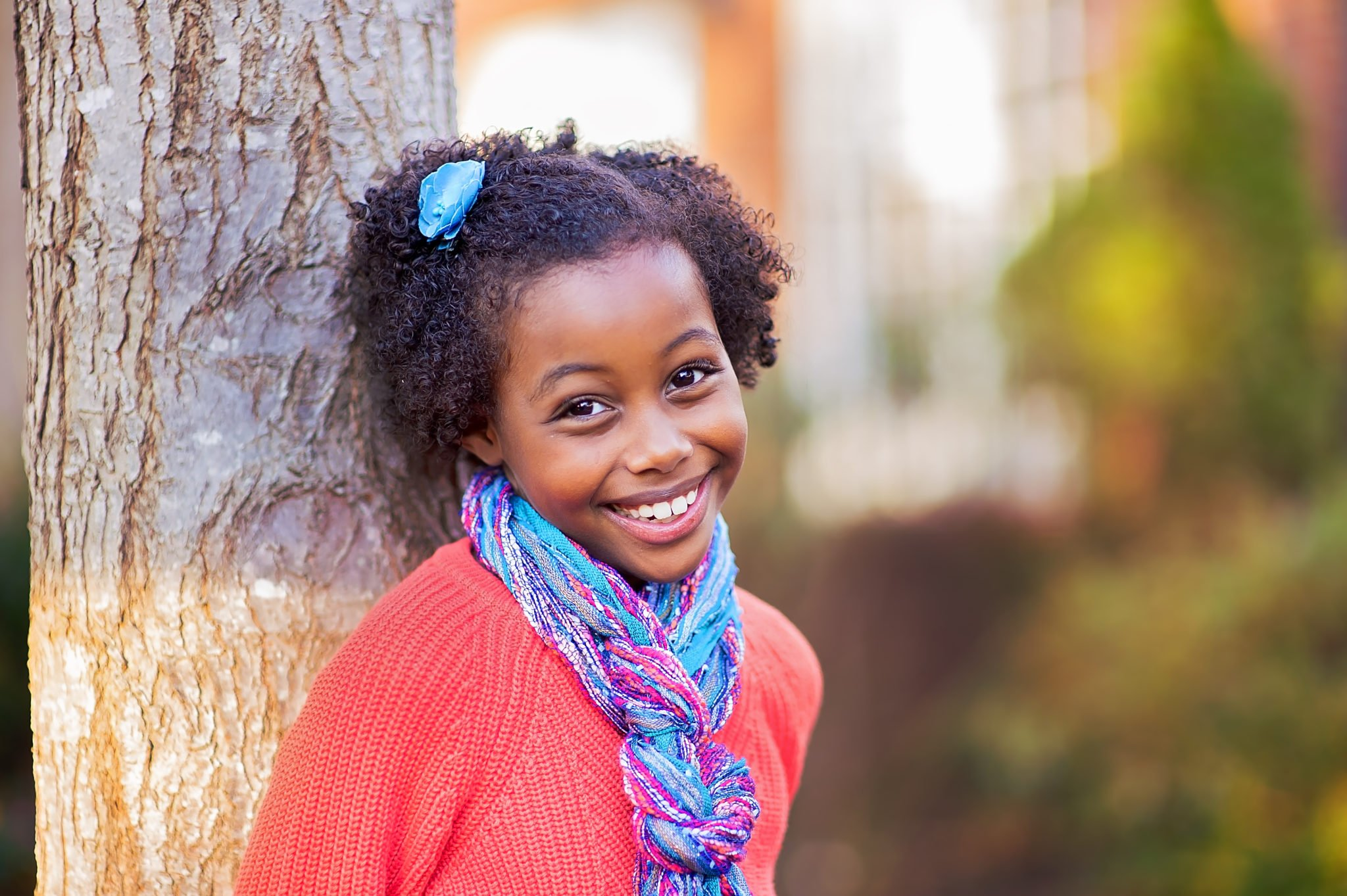 young African American girl wearing orange sweater and turquoise scarf