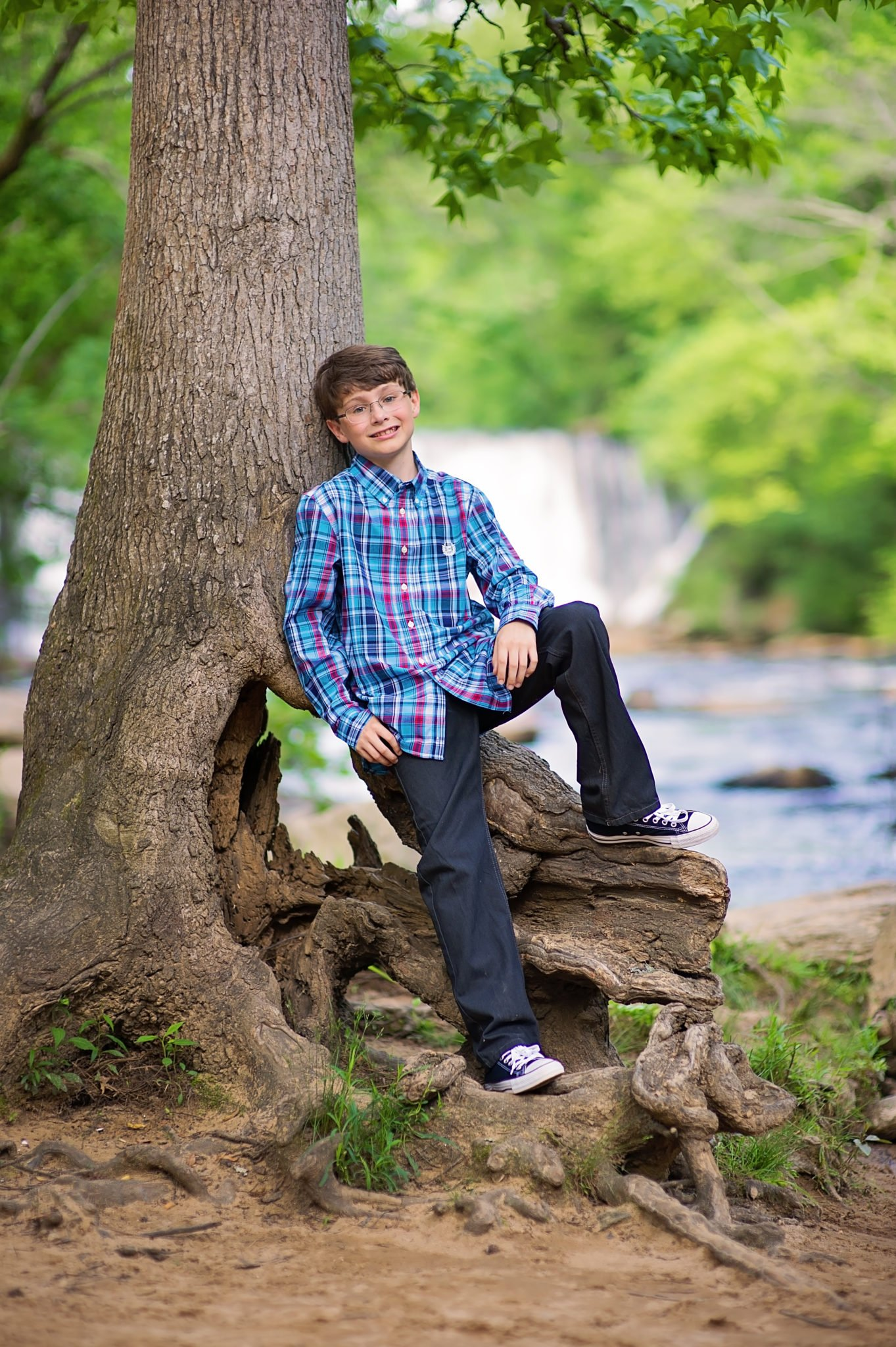 Young boy standing by tree wearing blue plaid shirt and jeans