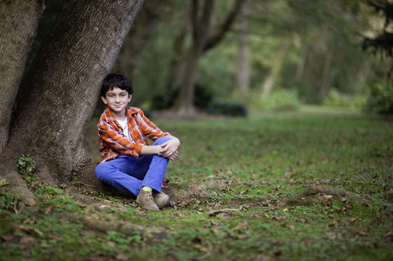 Young boy sitting by a tree wearing orange shirt and blue pants